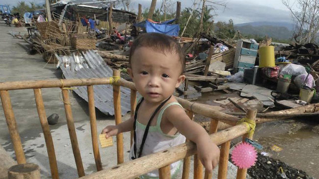 Un niño descansa entre los escombros de las casas dañadas por el paso del tifón Nock-Ten por la localidad de Polangui, provinc