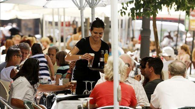 Una camarera sirve a unos turistas en la terraza de un restaurante