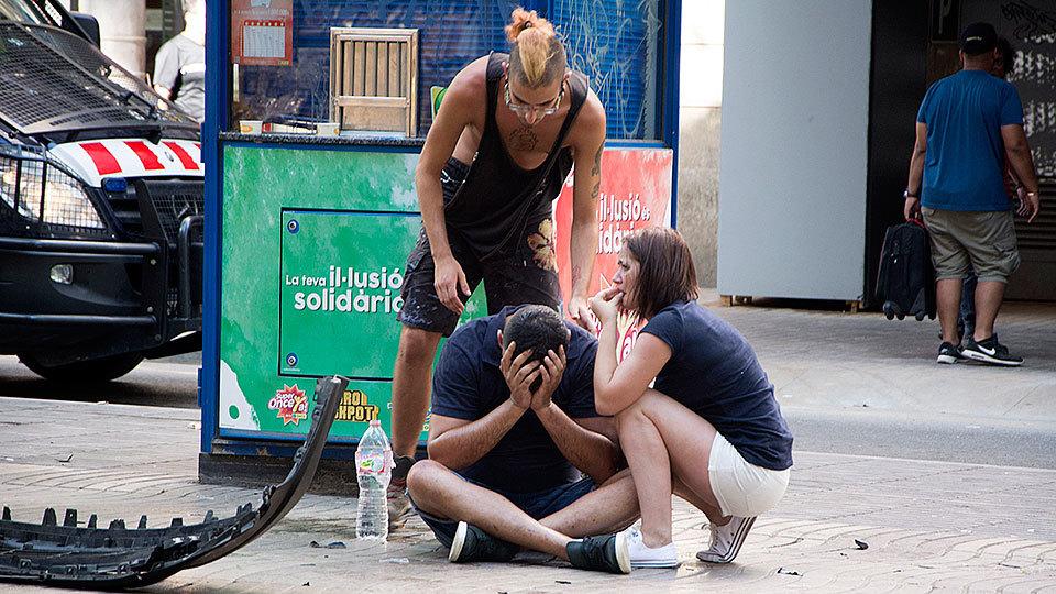 Varios jóvenes permanecen junto a los restos de un vehículo, en el lugar del atropello masivo realizado por una furgoneta que ha arrollado esta tarde a varias personas que paseaban por las Ramblas de Barcelona