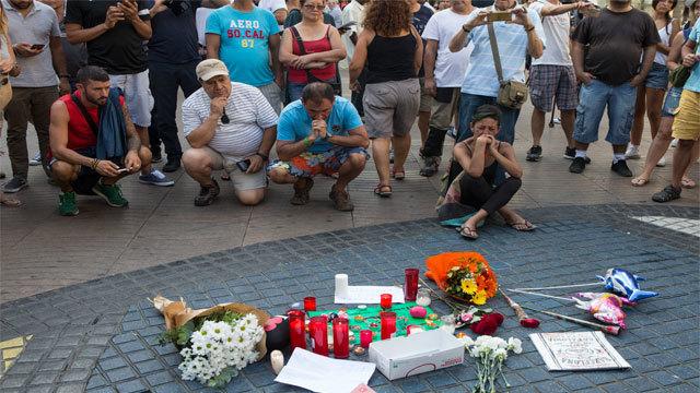 Varias personas se paran frente al mosaico de Miró en las Ramblas de Barcelona después del atentado