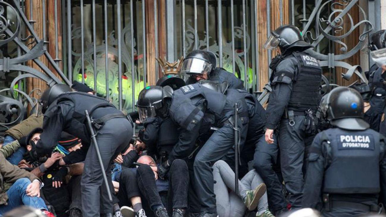 Agentes de los Mossos d'Esquadra desalojan a las decenas de personas se han concentrado a primera hora de esta mañana ante el