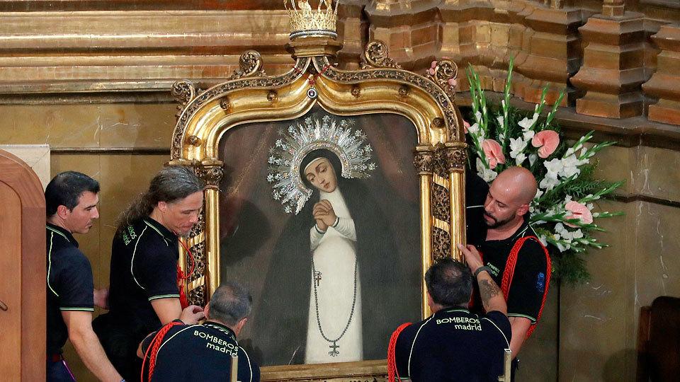 Momento del descenso del cuadro de la Virgen de la Paloma, patrona del Cuerpo de Bomberos de Madrid