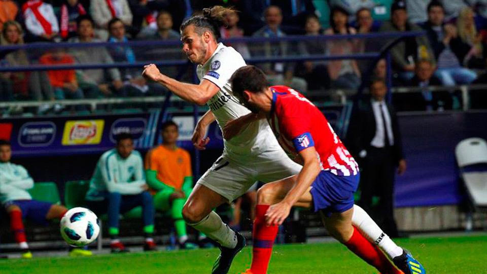 Gareth Bale disputa el balón con Diego Godín