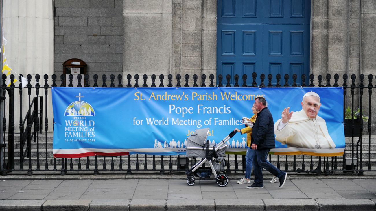 Una familia camina delante de una pancarta con la imagen del papa Francisco situada fuera de una iglesia en Dublín