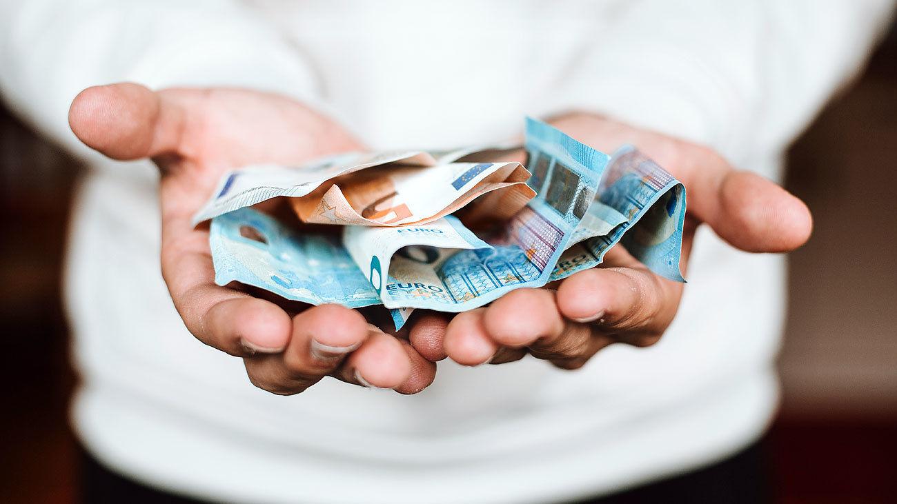 Varios billetes de euro sobre una mano