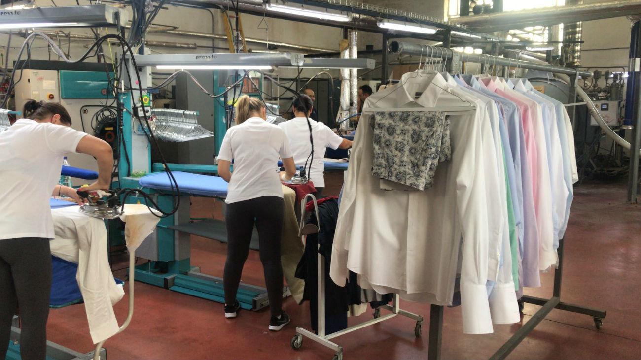 Empleados realizando labores de planchado en la tintorería