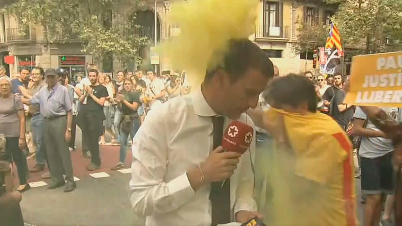 Un reportero de Telemadrid interrumpe su conexión por un bote de humo encendido durante la manifestación del 1-O
