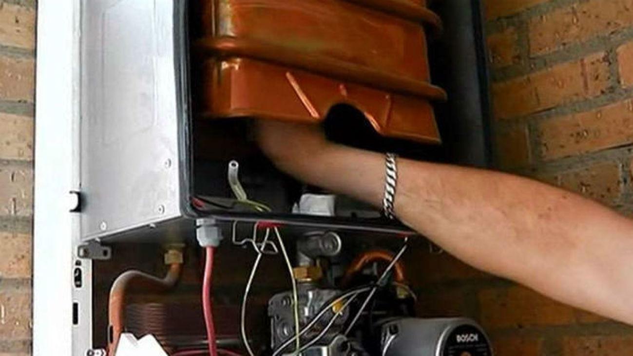Un instalador reparando una caldera de gas.