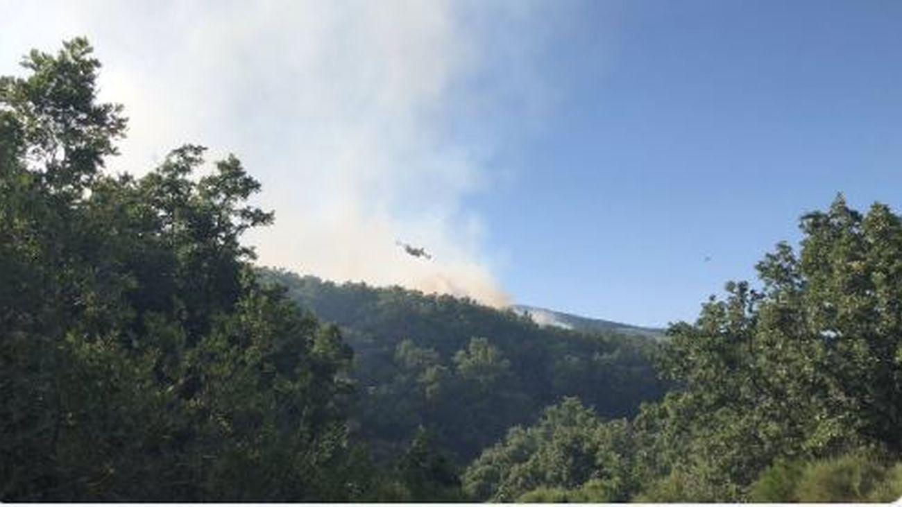 Medios aéreos y terrestres combaten un incendio en Robregordo, en Madrid