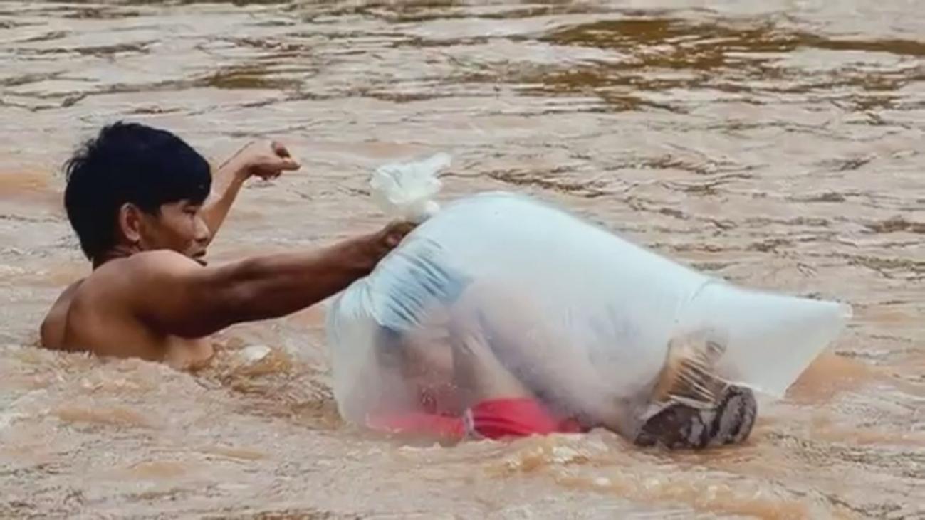 Niños en bolsas de plástico para cruzar un río e ir al colegio en Vietnam