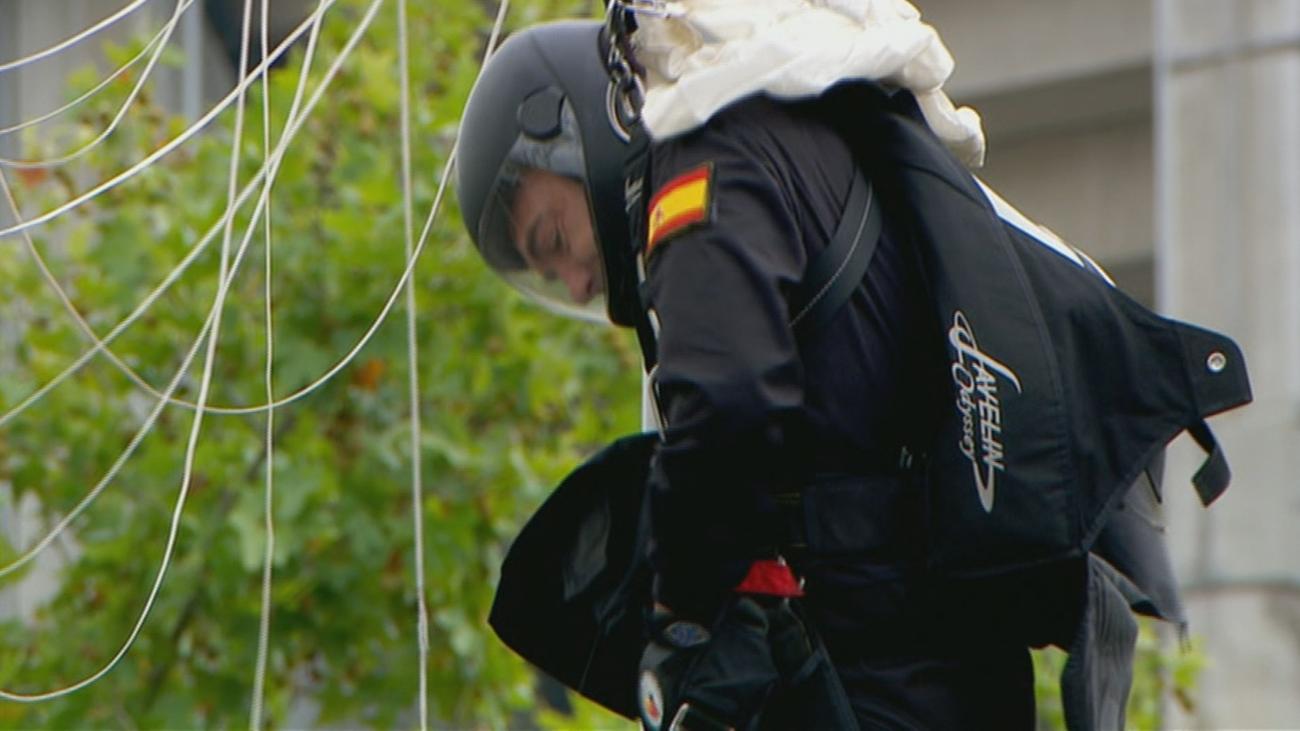 El paracaidista que porta la bandera se engancha en una farola