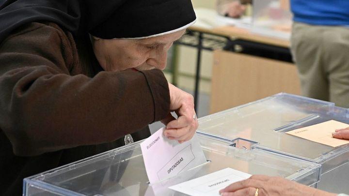 Una religiosa deposita su voto en la urna de un colegio electoral en Alcalá de Henares