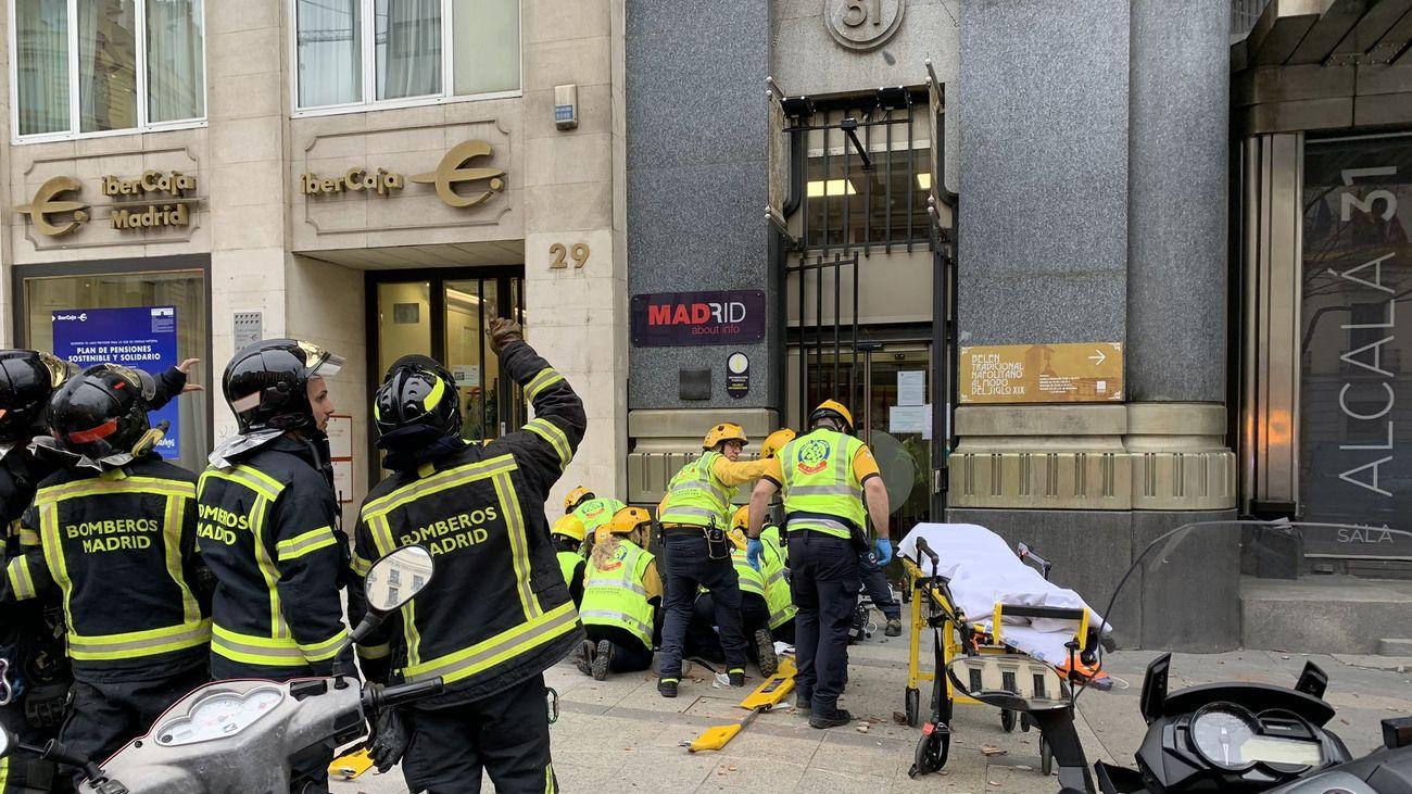 Sanitarios atienden a la mujer coreana que finalmente falleció tras recibir el impacto de unos cascotes en la calle Alcalá