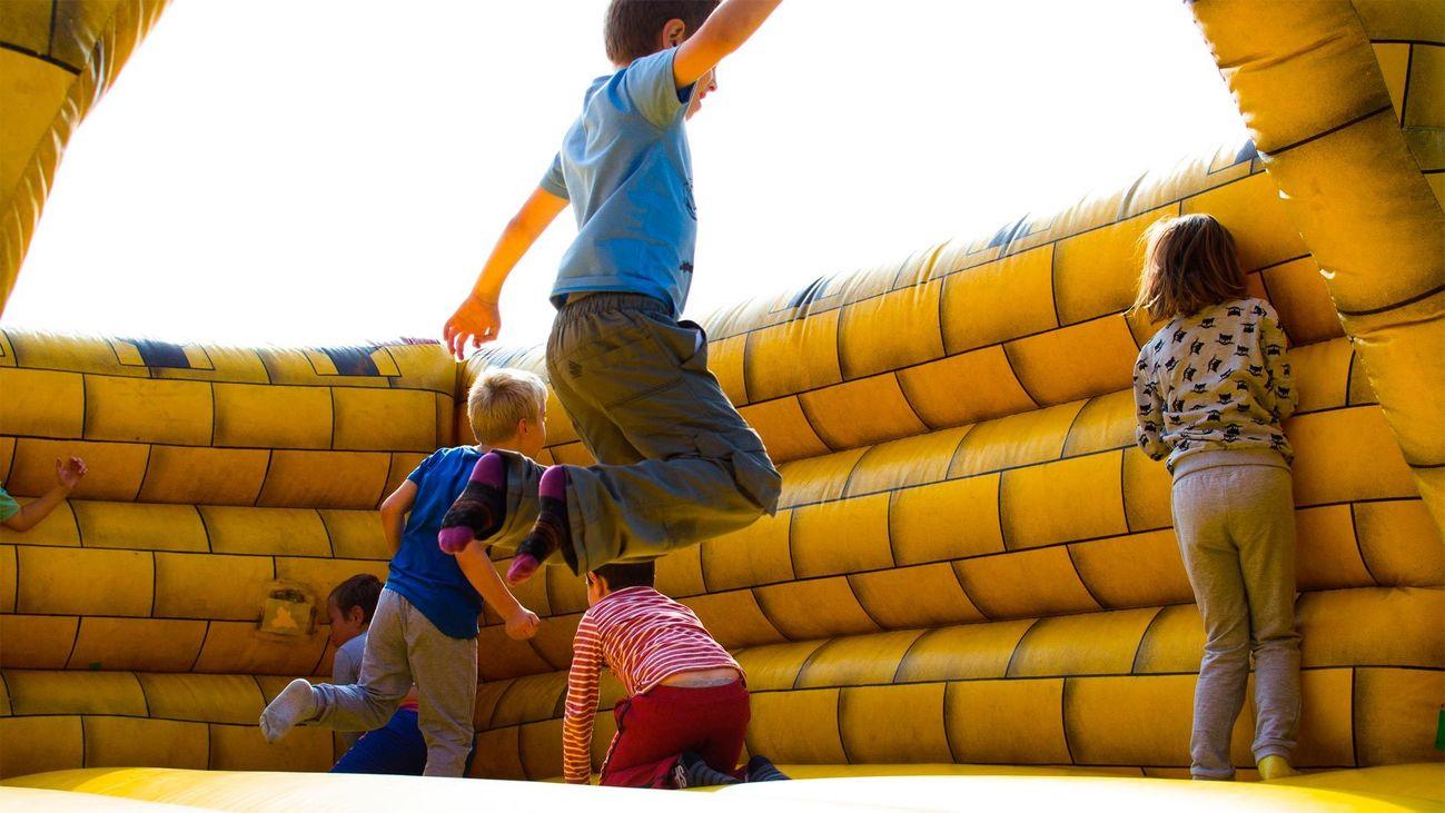 Niños y niñas juegan en un parque infantil