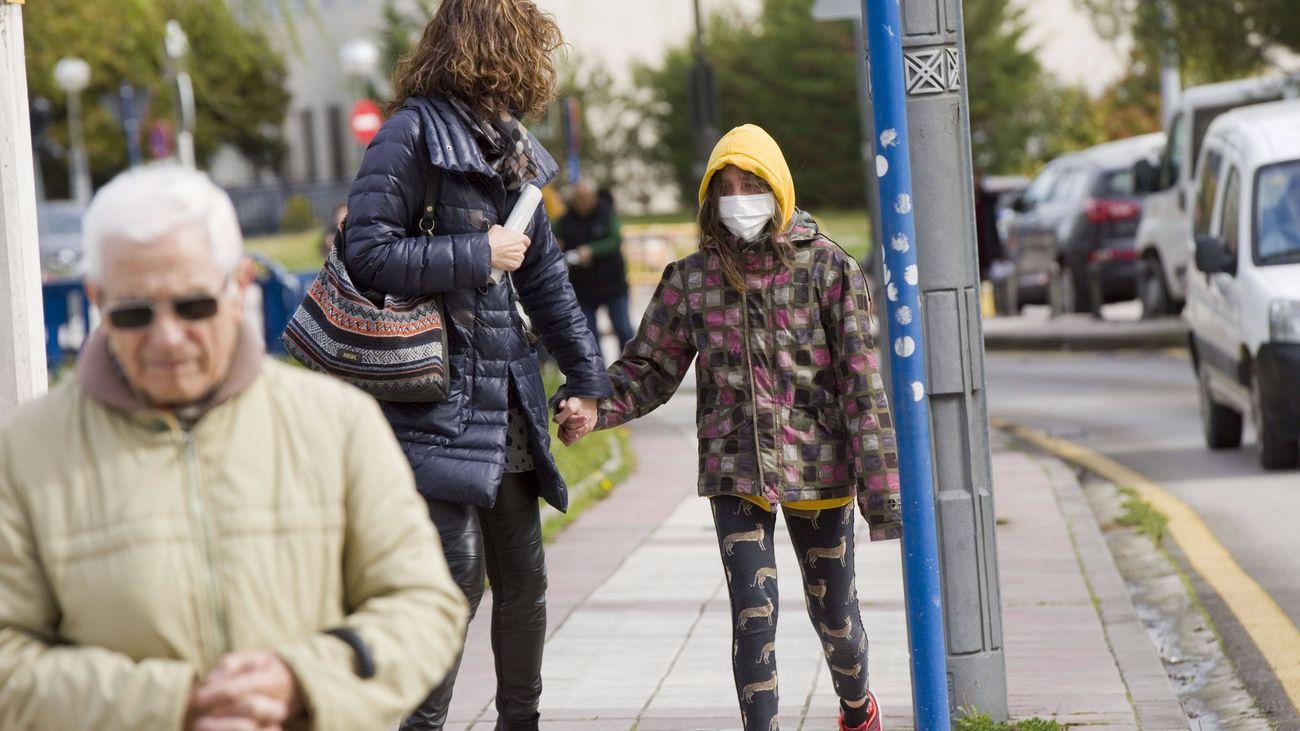Una niña pasea por la calle con una mascarilla