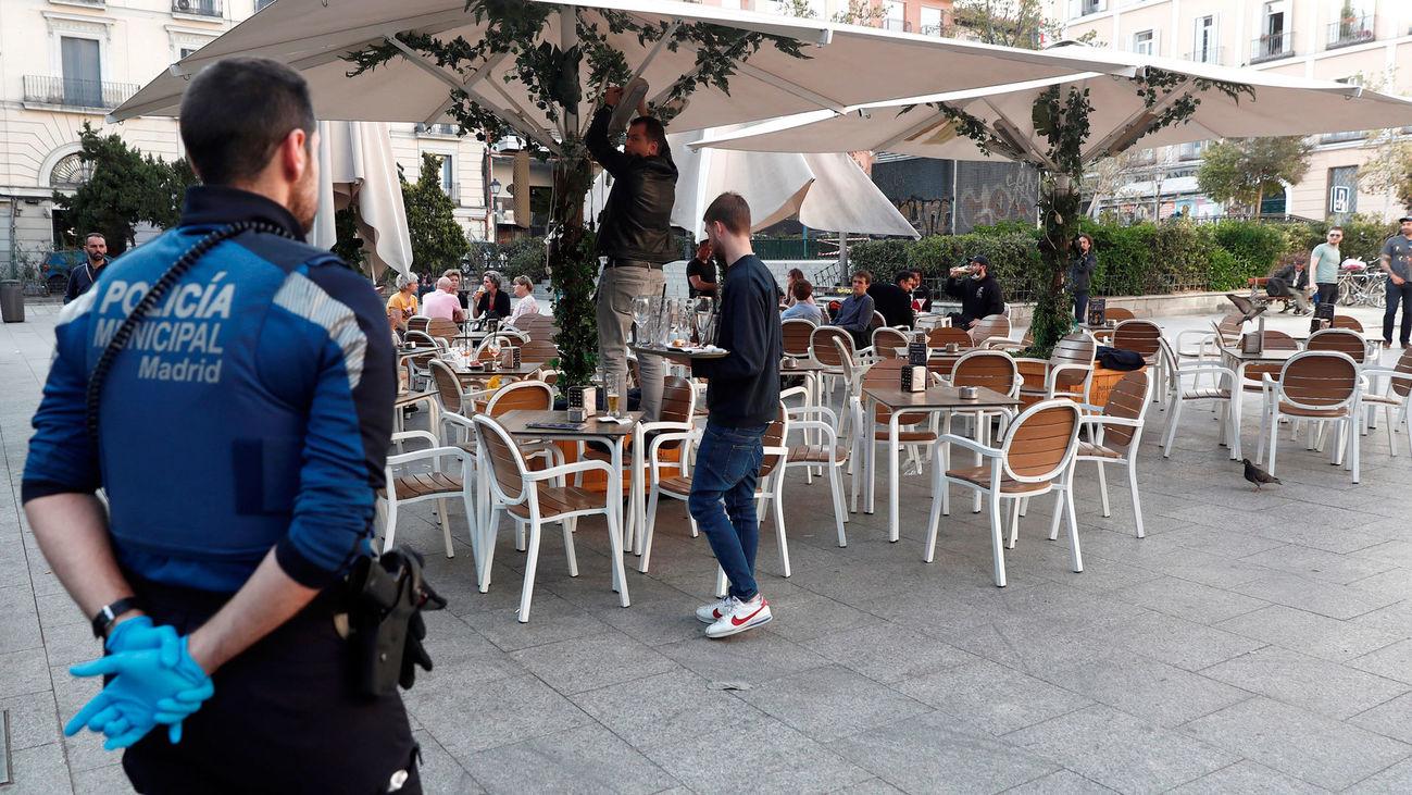 Un policía municipal de Madrid supervisa el cierre de una terraza en la crisis de coronavirus