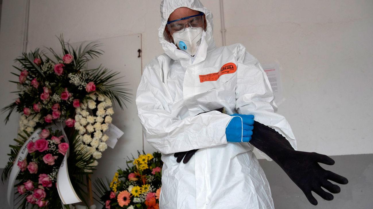 Un empleado funerario se protege con un Equipo de Protección Individual (EPI)en el Cementerio Jardín de Alcalá de Henares, durante el confinamiento por el coronavirus