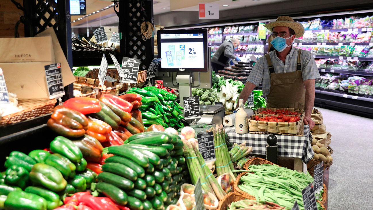 Un empleado con mascarilla y guantes en un supermercado en Madrid
