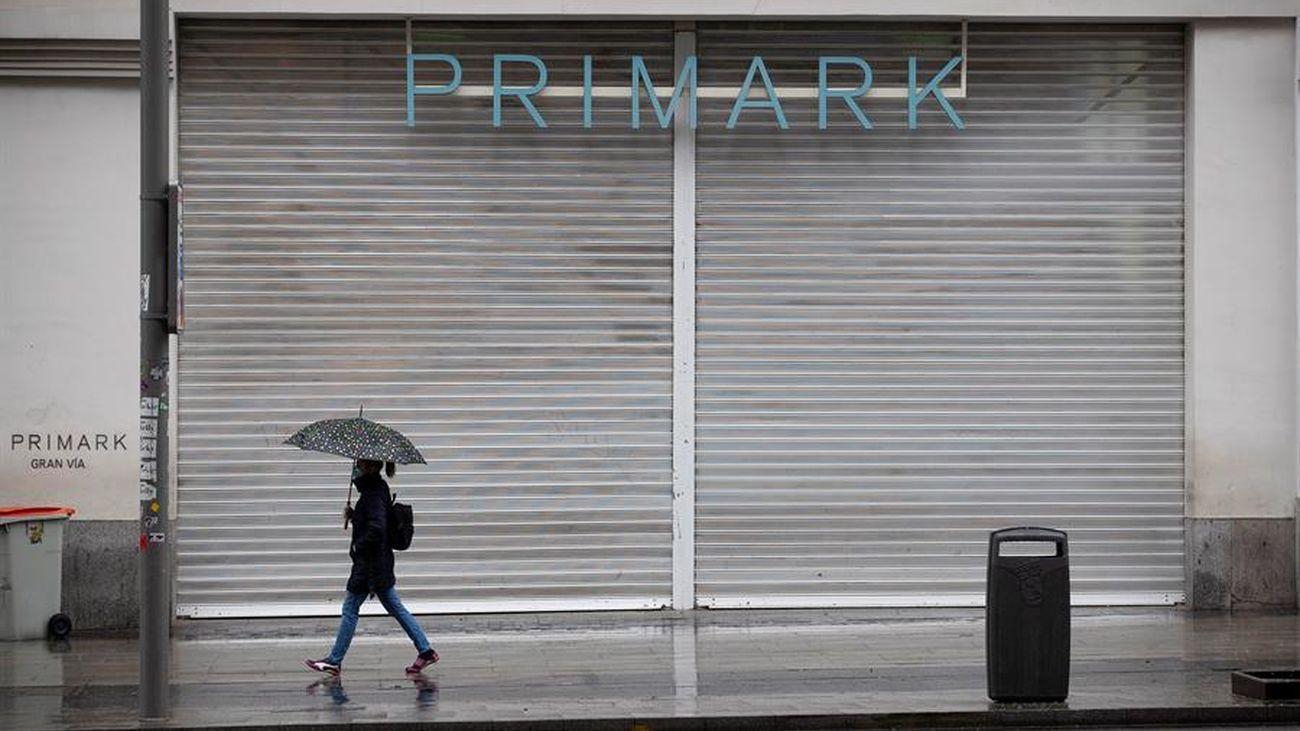 Una joven camina ante la tienda de Primark cerrada en Gran Vía por el coronavirus
