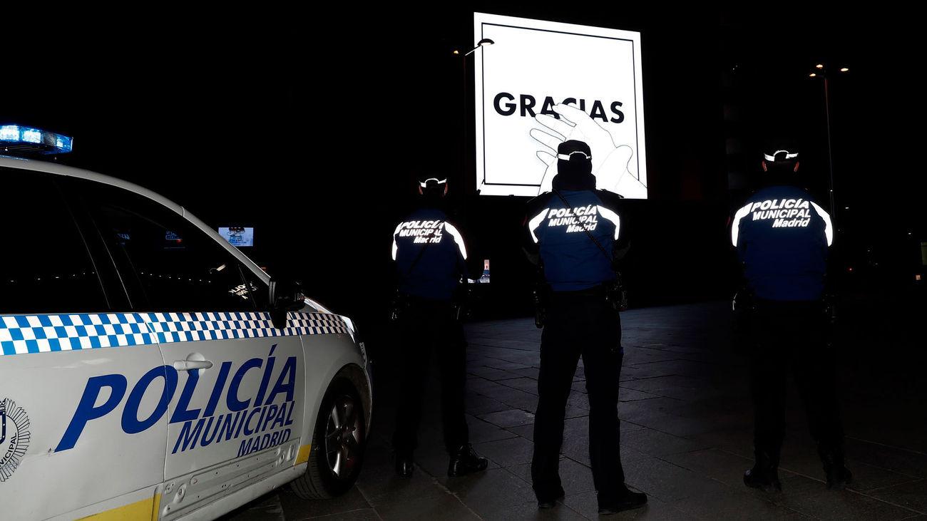 Agentes de la Policía Municipal de Madrid frente a un luminoso con la campaña 'Gracias' del Ayuntamiento de Madrid