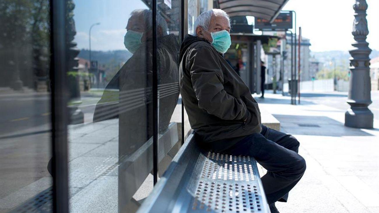 Una persona espera el autobús con una mascarilla puesta