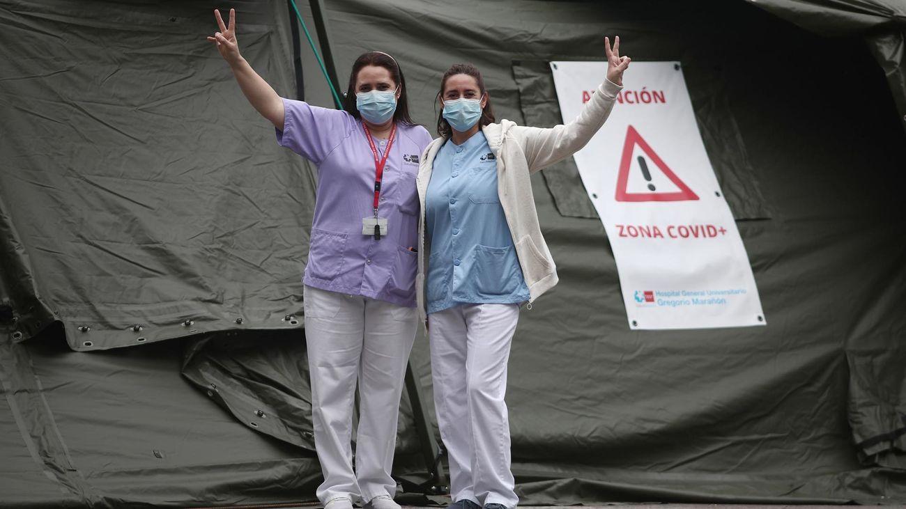 Dos sanitarias saludan frente al hospital de campaña instalado junto al Gregorio Marañón