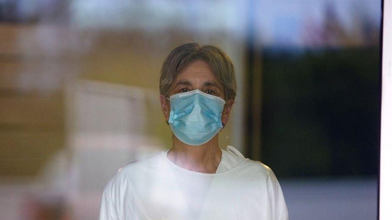 Una mujer con máscara sanitaria mira tras un cristal