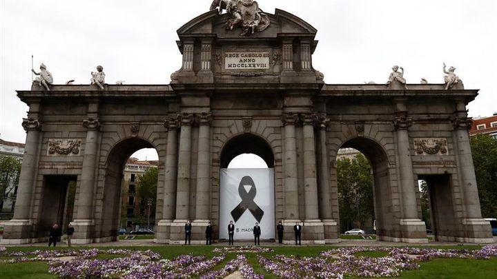 Un crespón negro en la Puerta de Alcalá para recordar a los fallecidos por el coronavirus