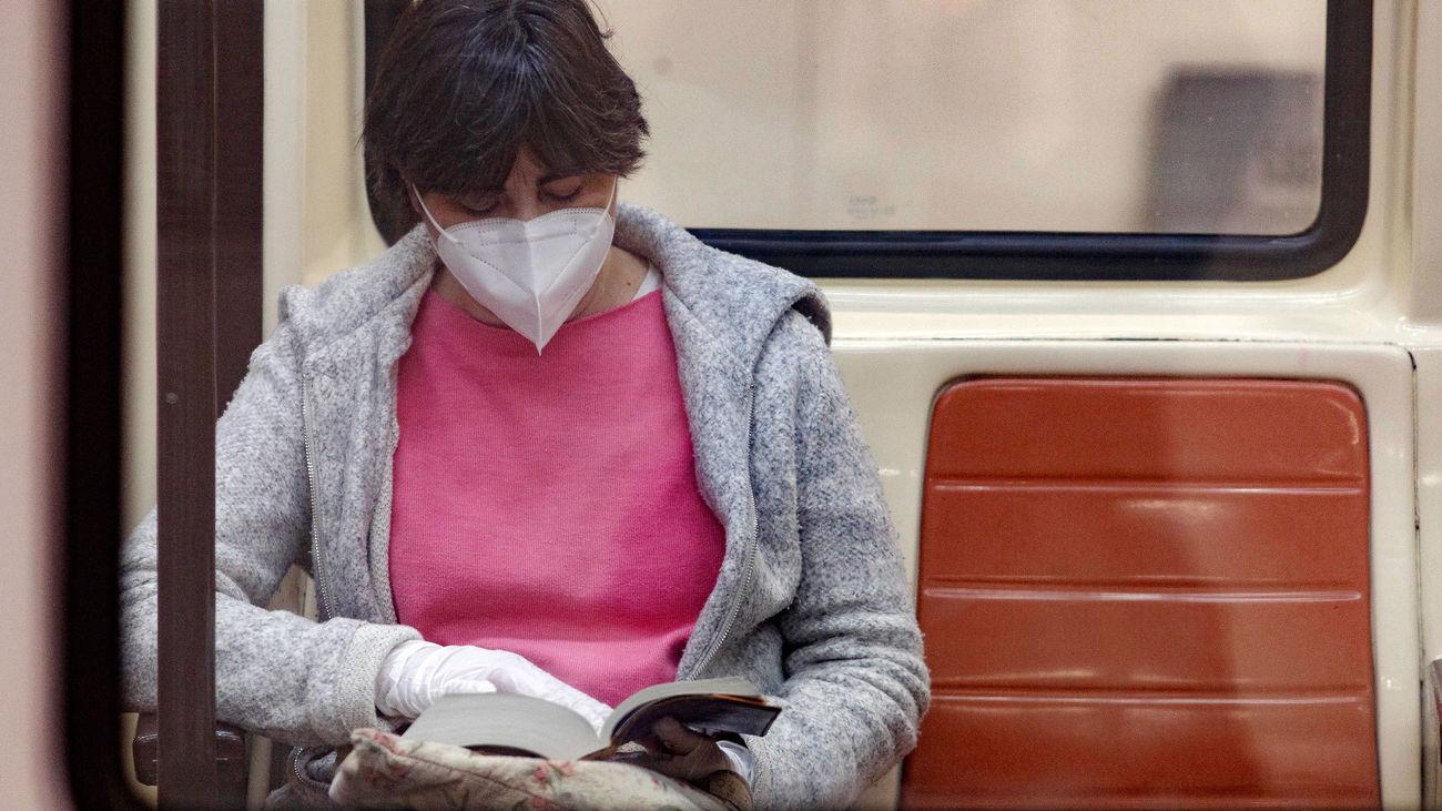 Una pasajera con mascarilla y guantes lee en un vagón del Metro de Madrid