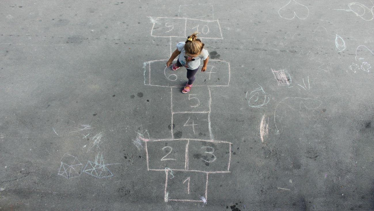 Niña jugando a la rayuela en la calle