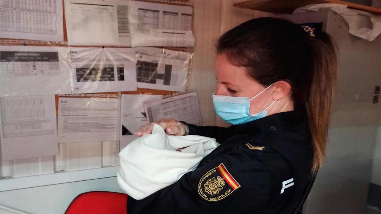 El bebé abandonado en un carro de un supermercado en Ávila en brazos de una Policía Nacional
