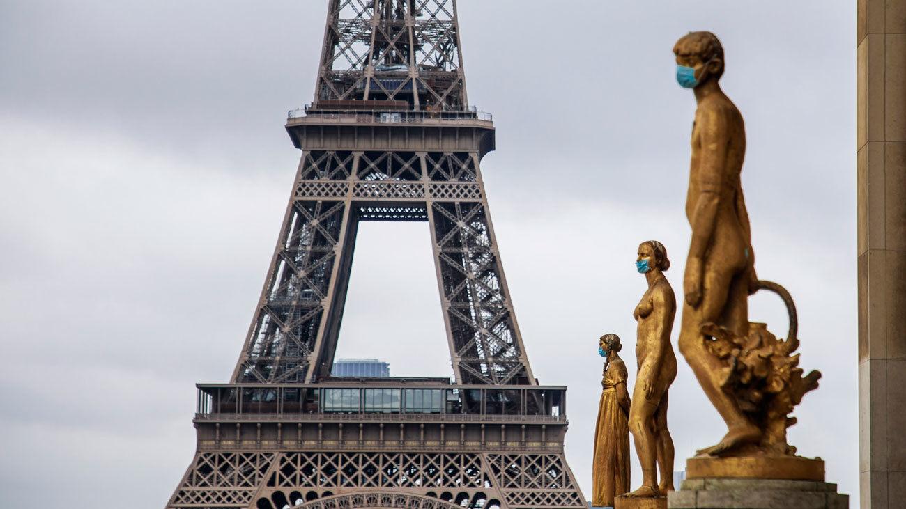 Las estatuas doradas de la Plaza de Trocadero, en París, aparecen este domingo adornadas con mascarillas de protección, con la Torre Eiffel de fondo.