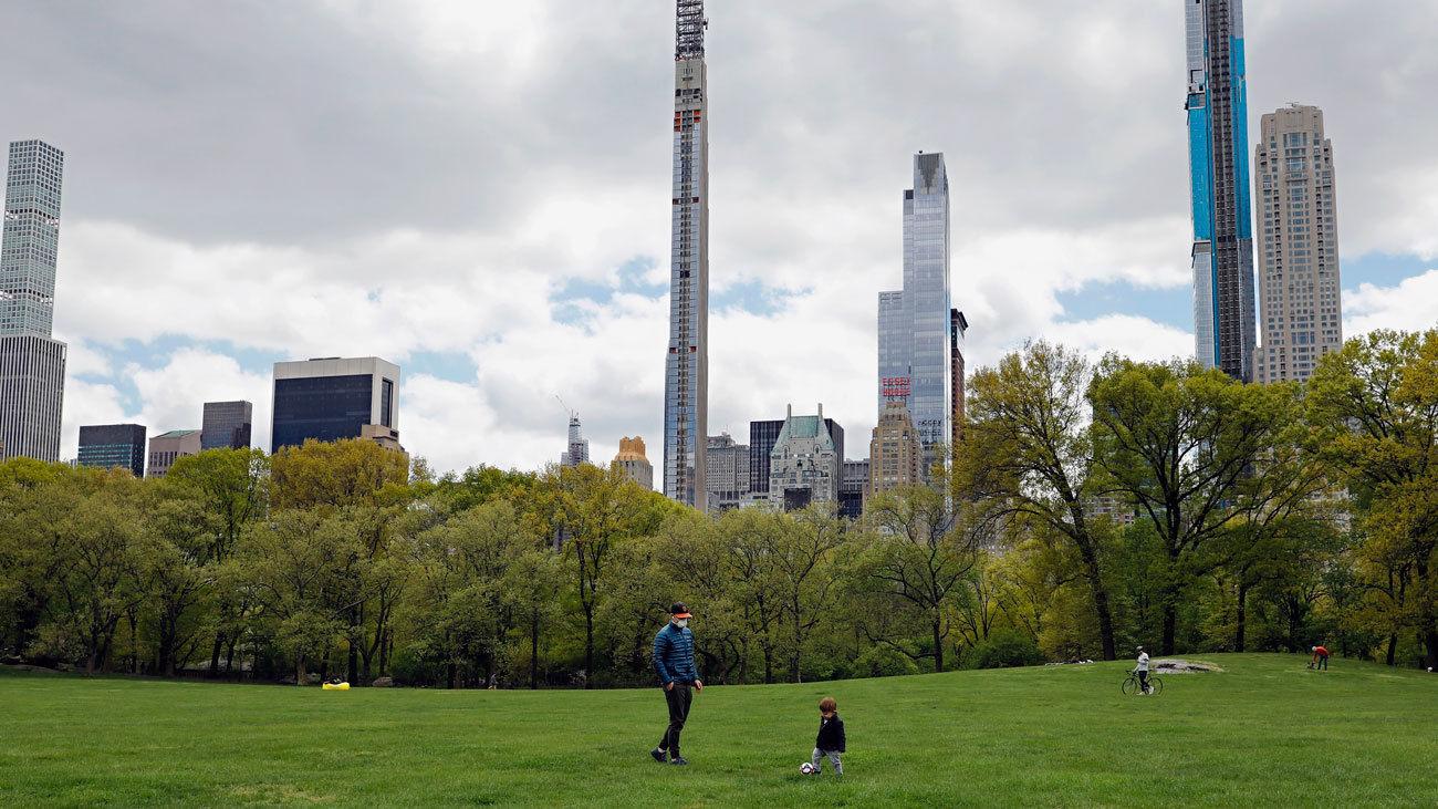 un padre juega al fútbol con su hijo en el Central Park