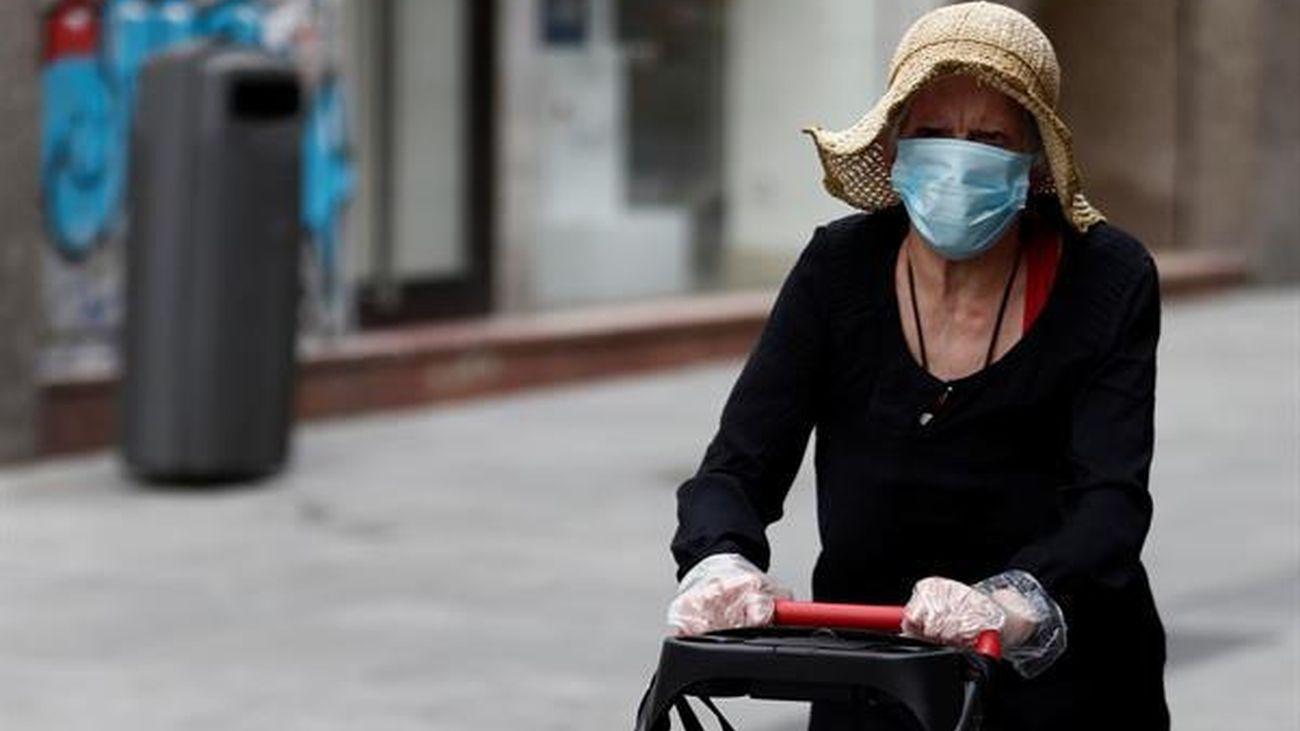 Una mujer pasea con una mascarilla puesta por una calle de Madrid