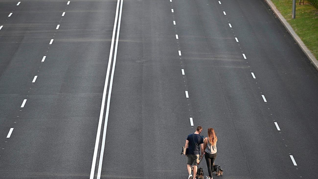 Una pareja pasea a sus perros en una de las vías peatonalizadas de Madrid