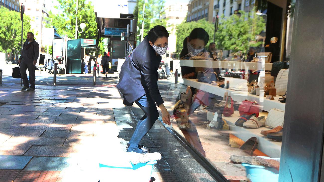 La empleada de una zapatería limpia el escaparate del comercio en la reapertura, tras el parón en la actividad por el estado de alarma