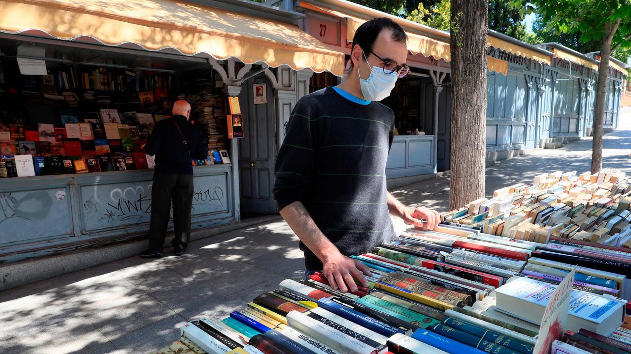 Una persona busca libros en un puesto de la Cuesta de Moyano, reabierto tras el cierre decretado por el covid-19