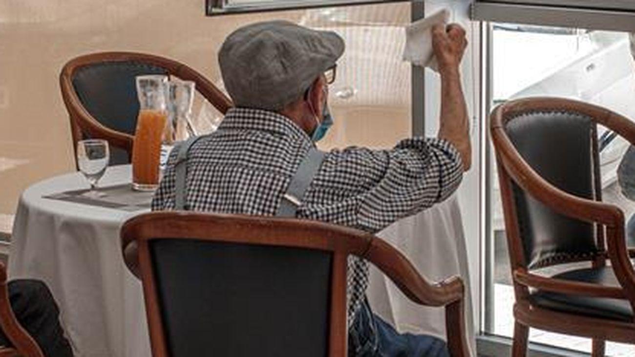 Una persona conversa con sus padres a través de una ventana habilitada en una residencia de mayores