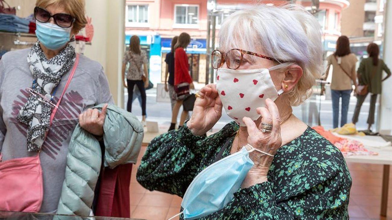 Varias mujeres con mascarilla, en una tienda