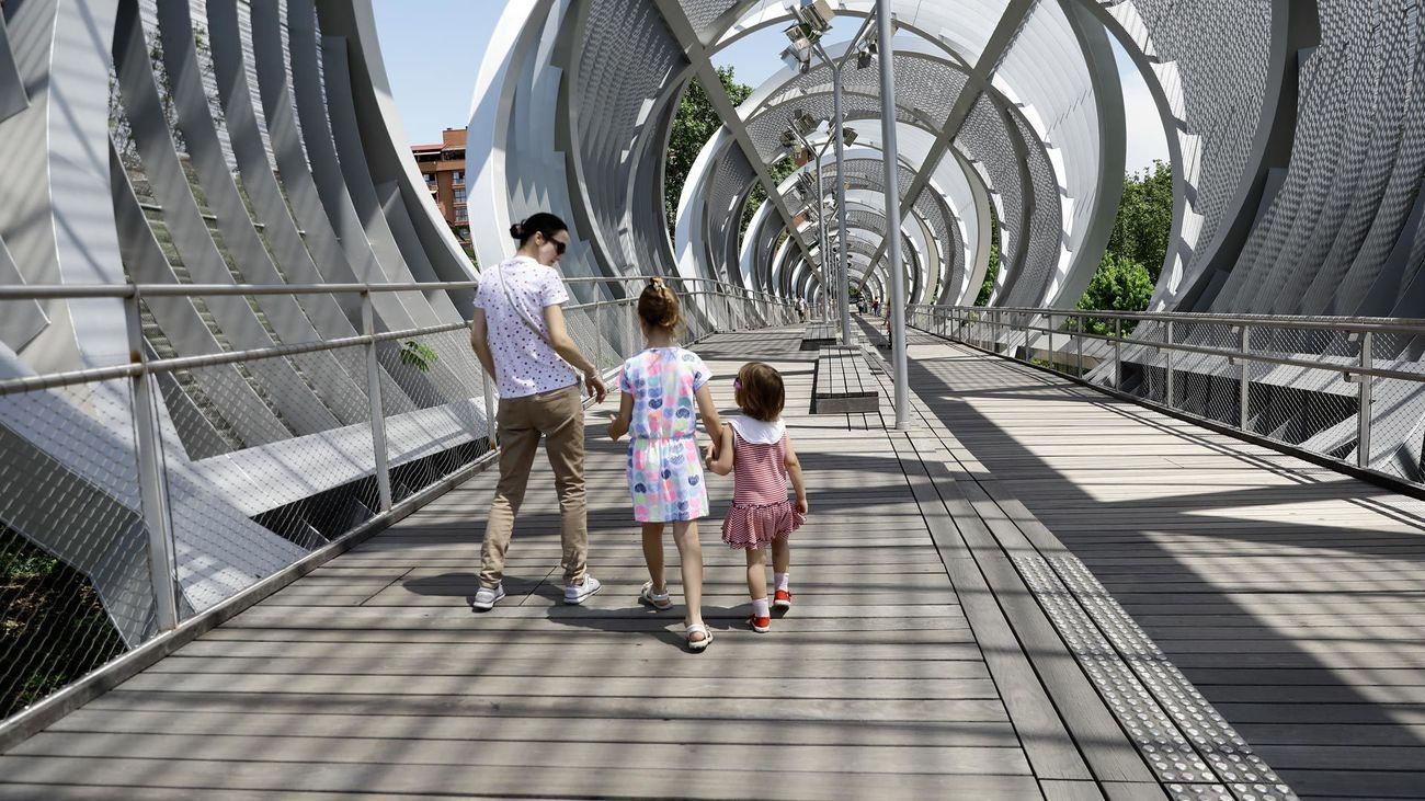 Una mujer pasea junto a sus hijas por Madrid Río, abierto en la fase 1 de desescalada