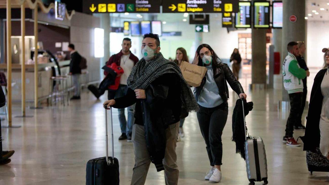 Pasajeros con mascarillas por el coronavirus en un aeropuerto