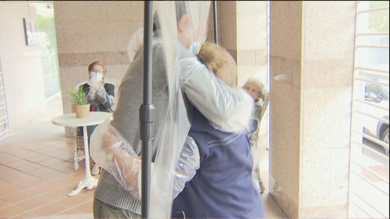 Reencuentros familiares con abrazos plastificados en las residencias de mayores de Madrid