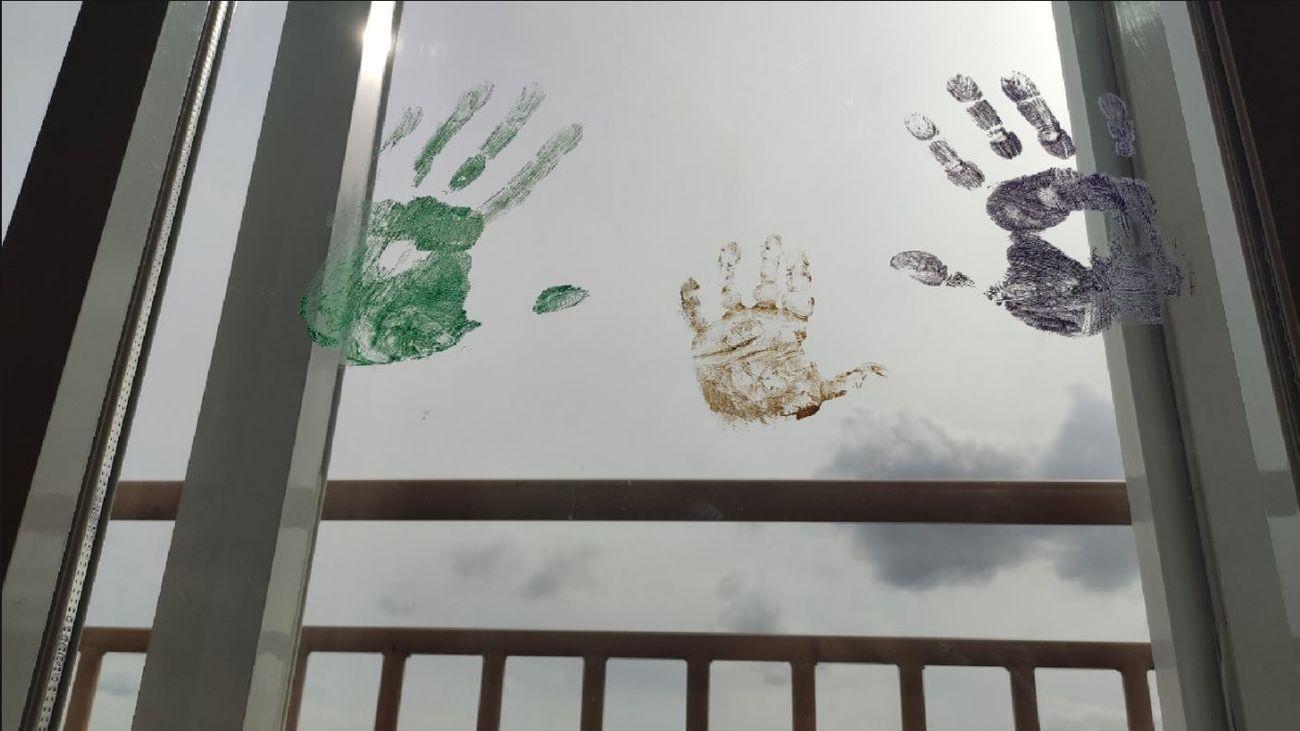 Manos pintadas en una ventana