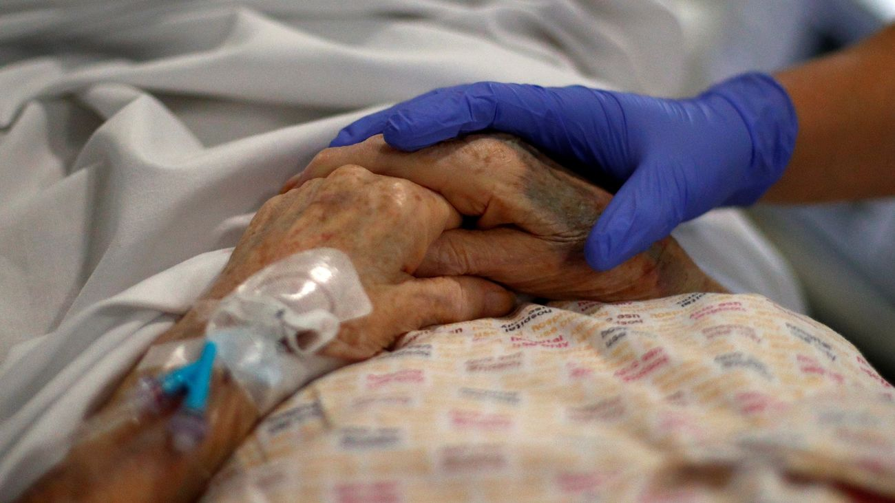 Detalle de la mano de un médico sobre la de un paciente anciano