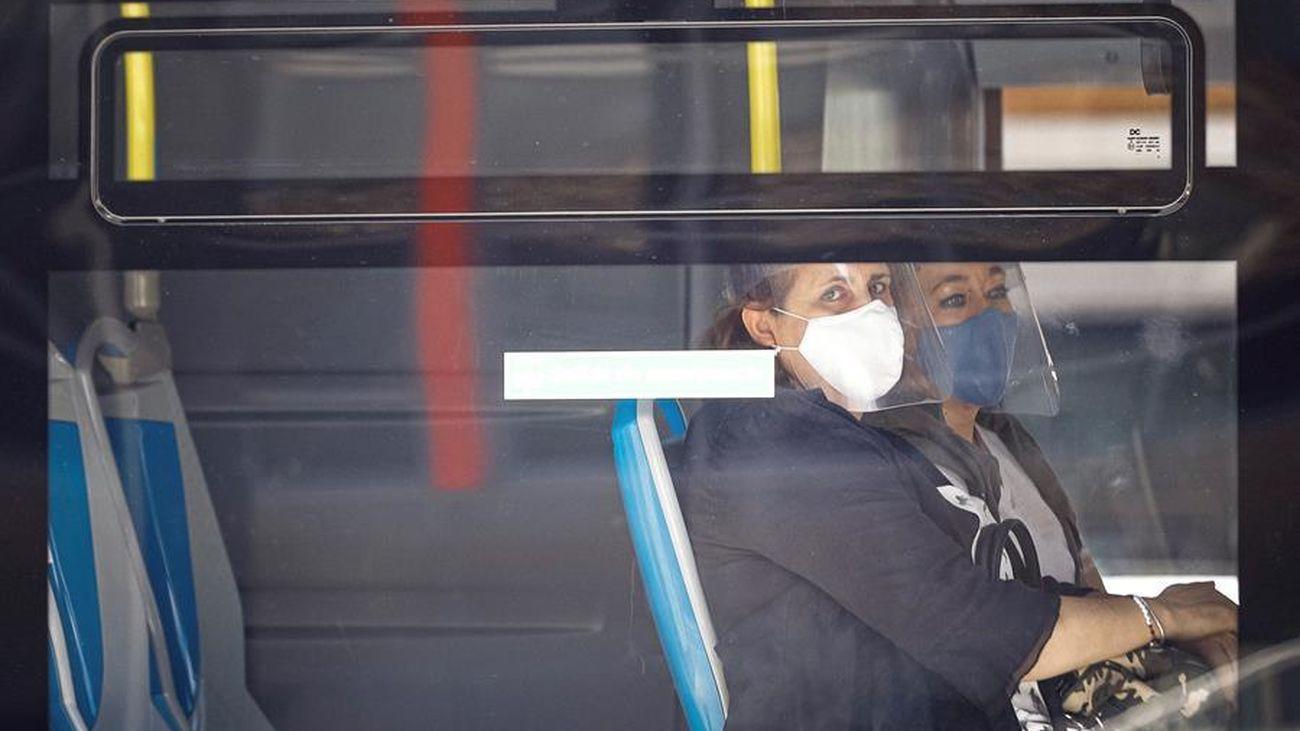 Dos mujeres con mascarilla y pantalla se sientan al lado en un autobús de Madrid