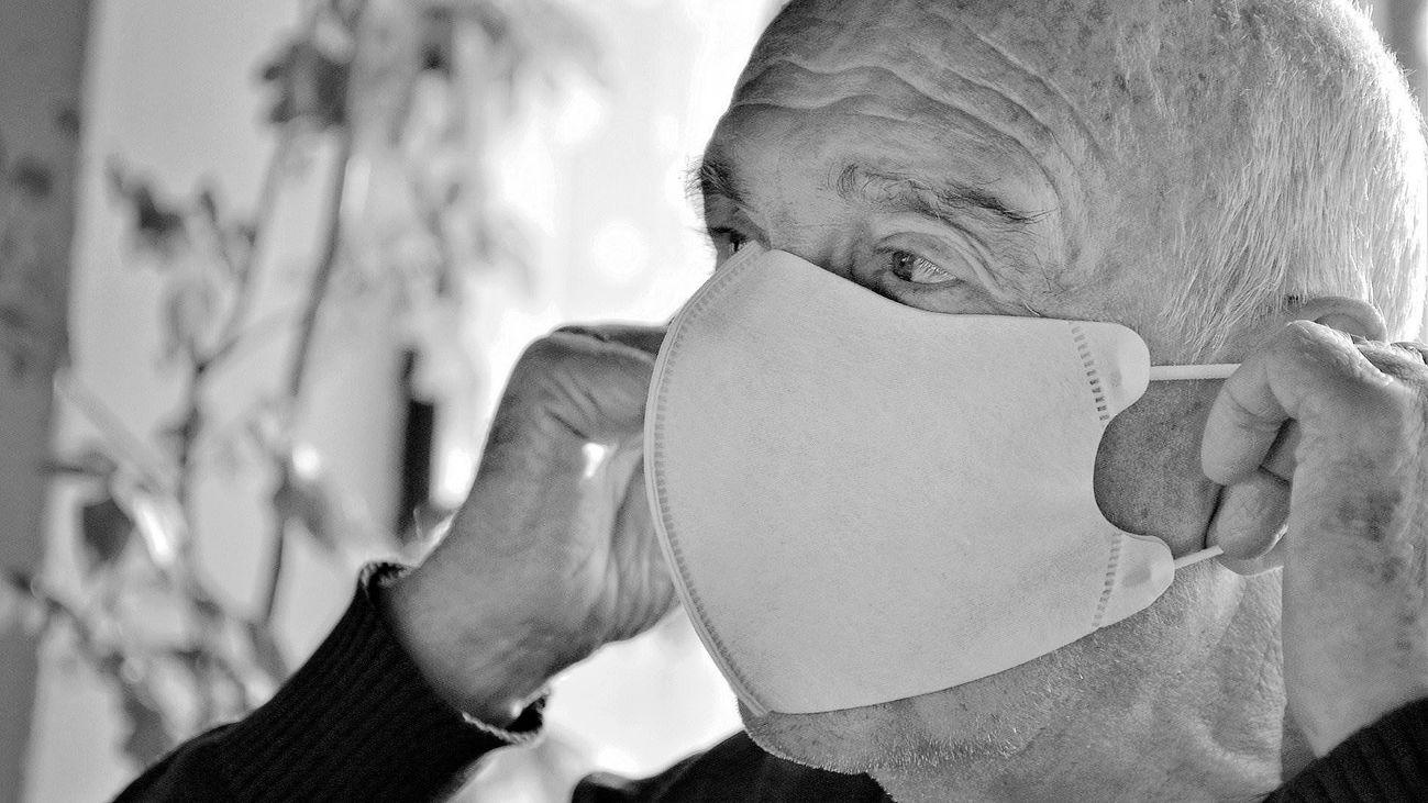 Un hombre mayor se coloca la mascarilla