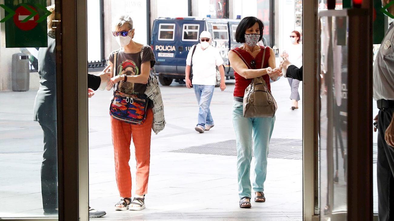 Dos mujeres se aplican desinfectante en las manos antes de entrar a un centro comercial