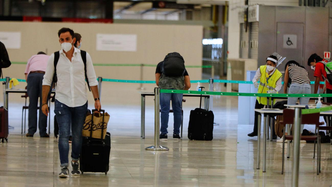 Viajeros pasan un control sanitario a su llegada a Barajas