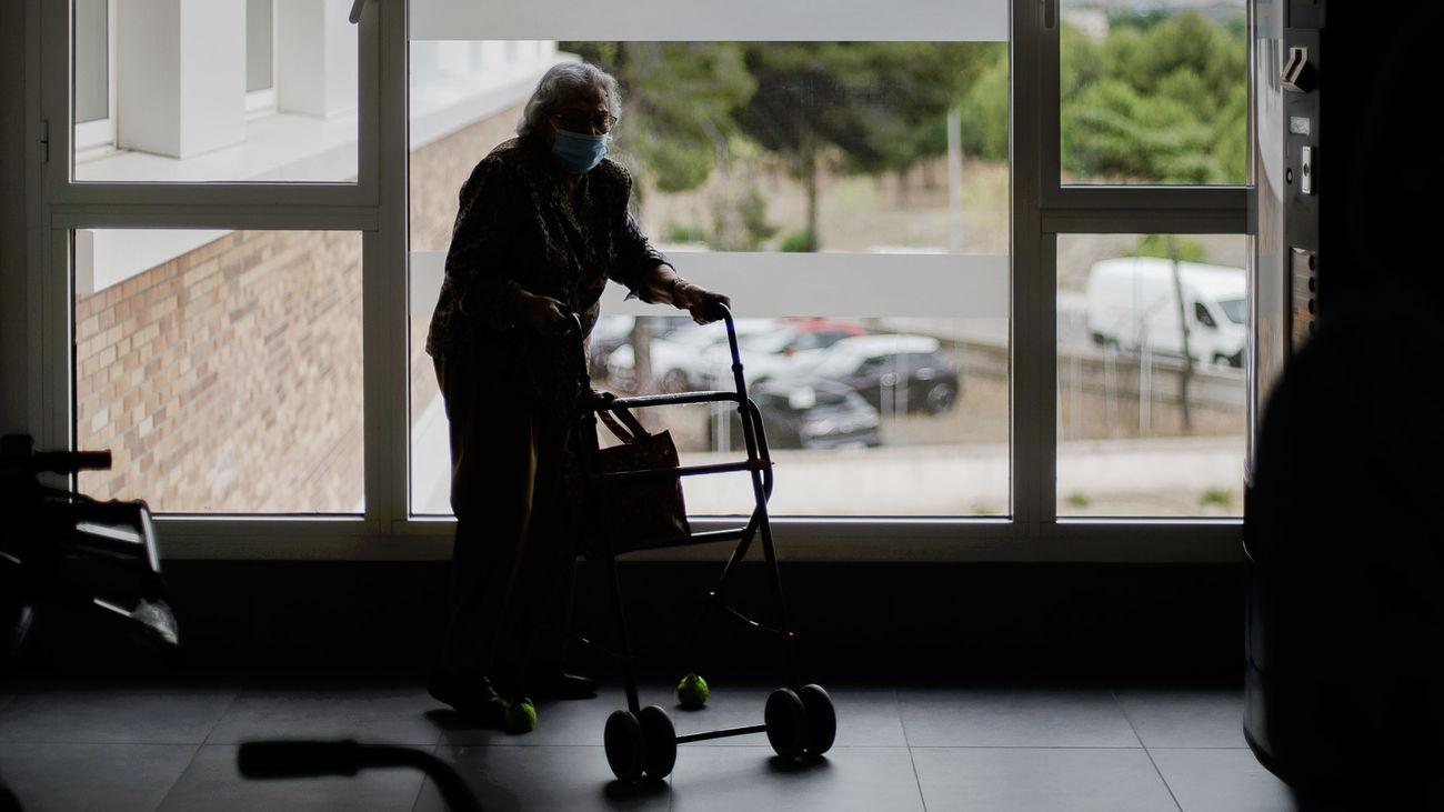 Una anciana se desplaza con andador en una residencia de la Comunidad de Madrid
