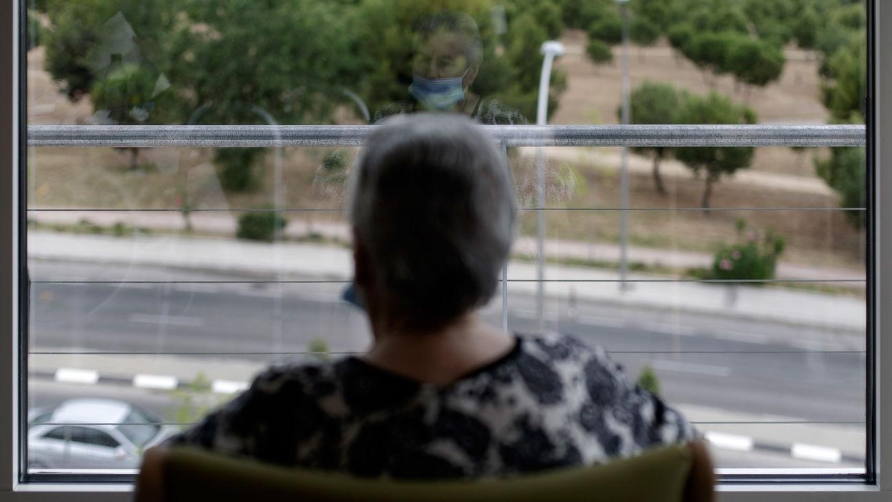 Una anciana mira por la ventana en una una residencia de la Comunidad de Madrid